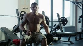 The bodybuilder does exercise with dumbbells. The bodybuilder does exercise for a bitseps of dumbbells stock video