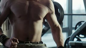 The bodybuilder does exercise with dumbbells. The bodybuilder does exercise for a bitseps of dumbbells stock footage