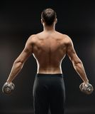 Bodybuilder does exercise with dumbbells Royalty Free Stock Image