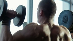 The bodybuilder does exercises for a back. With dumbbells stock footage