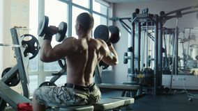 The bodybuilder does exercises for a back. With dumbbells stock video footage