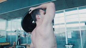 Bodybuilder does rotating exercise with barbell stock video footage