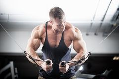 Bodybuilder doing butterfly on cable pull Stock Images