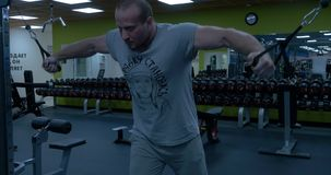 Bodybuilder doing butterfly on cable pull for better definition of his arm muscles. Bodybuilder man with naked torso stock footage