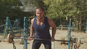 Bodybuilder doing deadlift exercise at outdoor gym stock footage