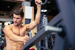 Bodybuilder doing exercise on fitness machine in gym Stock Photography