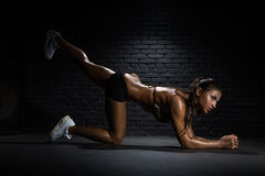 Bodybuilder doing exercises for buttocks. Sporty slim woman with ponytail doing exercises for buttocks Stock Image