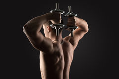 Bodybuilder doing exercises with dumbbells. Behind Stock Images