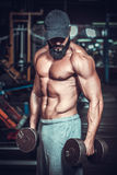 Bodybuilder doing exercises with dumbbells Royalty Free Stock Images