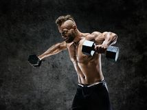 Bodybuilder doing the exercises with dumbbells. Photo of young man with naked torso on dark background. Strength and motivation stock photography