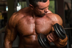 Bodybuilder doing heavy weight exercise for biceps with dumbbell stock images