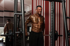 Bodybuilder Doing Heavy Weight Exercise For Trapezius Royalty Free Stock Photos