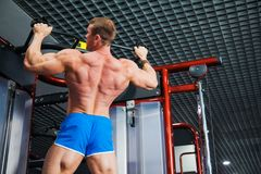 Bodybuilder doing pull-ups at modern gym. Young sportsman pull himself up on bar. Athlete chin up at sports club. Closeup, copy space Royalty Free Stock Photo