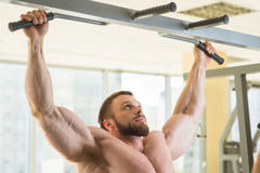 Bodybuilder doing pull-ups. stock photography
