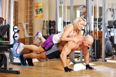 Bodybuilder is doing push-ups. With his female co-worker behind the back stock images