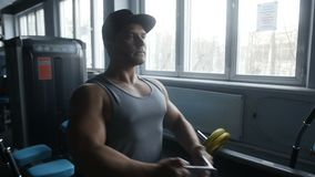 Bodybuilder is doing seated low row. In gym stock footage