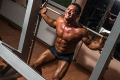 Bodybuilder doing squat with barbell in gym. Body builder doing squat with barbell in gym Royalty Free Stock Photos