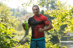 Bodybuilder Drinkwater van Shaker Outdoors In Nature royalty-vrije stock afbeeldingen