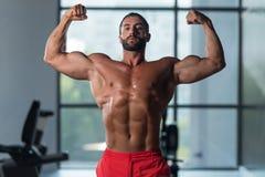 Bodybuilder-Eignungs-Modell Posing Double Biceps nach Übungen lizenzfreie stockfotografie