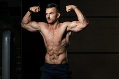 Bodybuilder-Eignungs-Modell Posing Double Biceps nach ?bungen stockbild