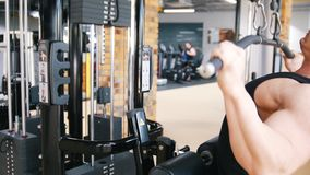 Bodybuilder in einem schwarzen Trägershirt führt eine Übung auf Schulter herunterziehen Maschinen durch stock footage