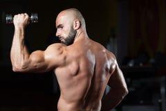 Bodybuilder exerçant des épaules avec l'haltère Photo stock