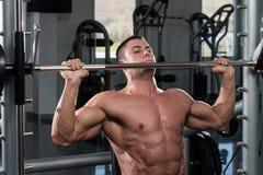 Bodybuilder exerçant des épaules avec le Barbell Image stock
