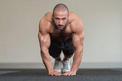 Bodybuilder exerçant des pousées sur le plancher Photos stock