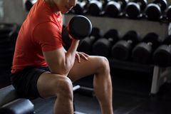 Bodybuilder exercise with dumbbell in gym. Strong Asian man bodybuilder sit and exercise biceps with heavy dumbbells with gym background. Muscular body sportsman stock images