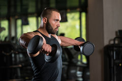 Bodybuilder Exercise Shoulders With Dumbbells Royalty Free Stock Photo