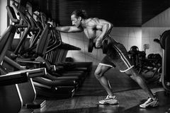 Bodybuilder Exercising Back With Dumbbell Stock Images