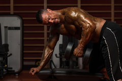 Bodybuilder Exercising Back With Dumbbells Stock Photos