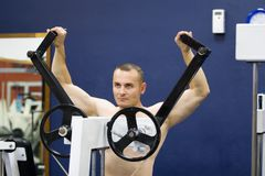 Bodybuilder exercising in gym. Half body portrait of bare chested young bodybuilder working out on weight machine in gym Royalty Free Stock Photography