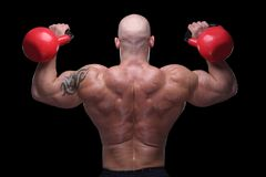 Cross fit guy. Bodybuilder exercising with kettlebells in front of black background Stock Photos