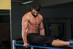 Bodybuilder Exercising On Parallel Bars Stock Photography