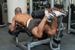 Bodybuilder faisant des exercices menteur de boucles de jambe sur la machine Image stock