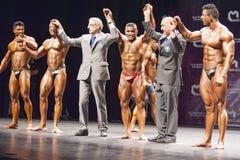 Bodybuilder feiern ihren Sieg auf Stadium mit Beamten Lizenzfreie Stockfotografie