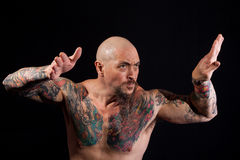 Bodybuilder in fighting stance. A mean-looking bodybuilder takes on a fighting stance stock photography