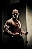 Bodybuilder fléchissant des bras Photographie stock libre de droits