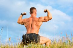 Bodybuilder flexing back muscles outdoors. Against blue sky Stock Images