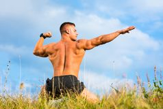 Bodybuilder flexing back muscles outdoors. Against blue sky Royalty Free Stock Image