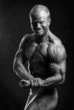 Bodybuilder flexing biceps Royalty Free Stock Images