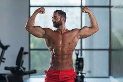 Bodybuilder Flexing Front Double Biceps Pose In Gym Royalty Free Stock Images