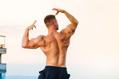 Bodybuilder flexing muscles on a rooftop. Young bodybuilder flexing muscles on a rooftop Royalty Free Stock Photography
