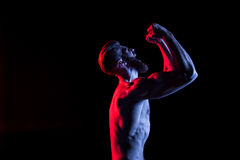 Bodybuilder gesturing and yelling isolated on black with dramatic lighting stock photo