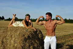 Bodybuilder with a girl in the countryside Royalty Free Stock Image