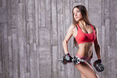 Bodybuilder girl with dumbbell Royalty Free Stock Image
