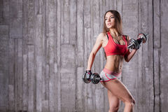 Bodybuilder girl with dumbbell Royalty Free Stock Photo