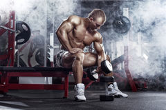 Bodybuilder guy execute exercise with dumbbells Stock Photo