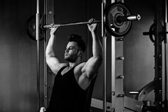 Bodybuilder guy in gym with heavy weights  monochrome Royalty Free Stock Image